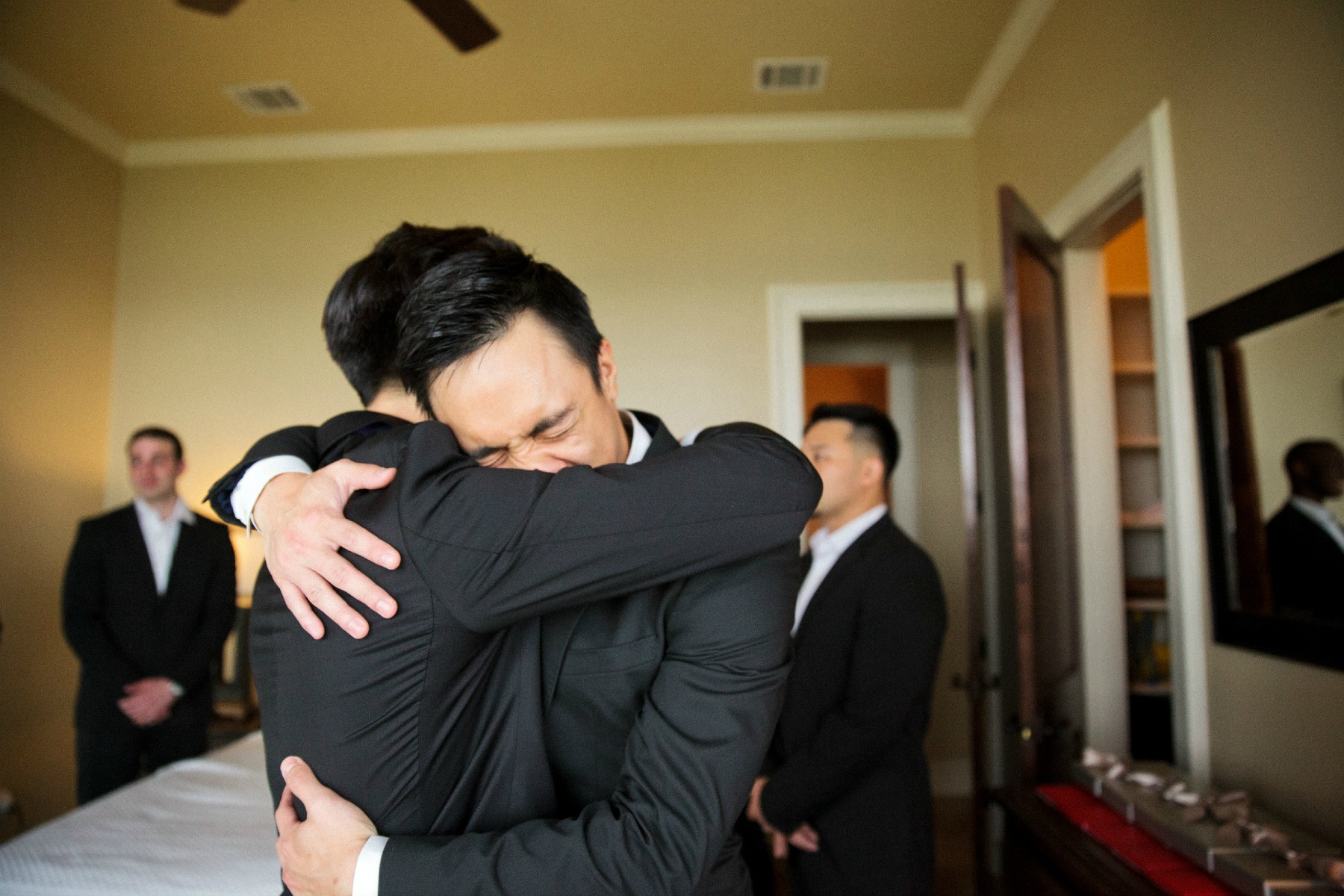 groom and best friend hug in an emotional moment
