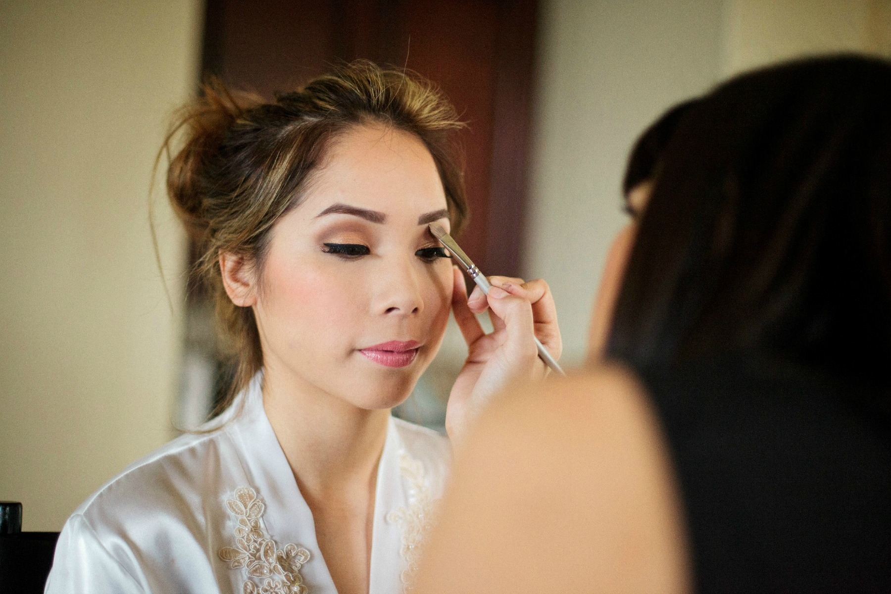makeup artist putting eyeshadow on the bride