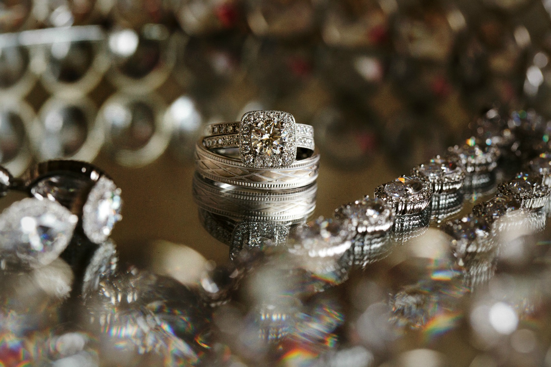 sparkling wedding jewelry displayed on a glass tray
