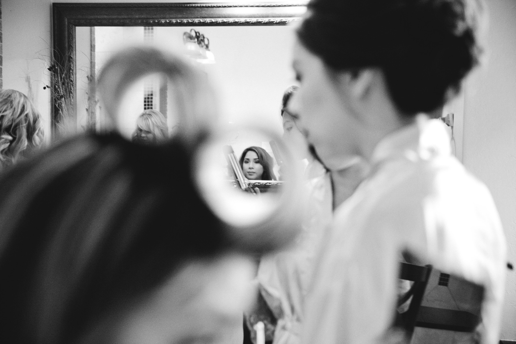 creative getting ready shot of brides mirror reflection taken through a bridesmaids rollers