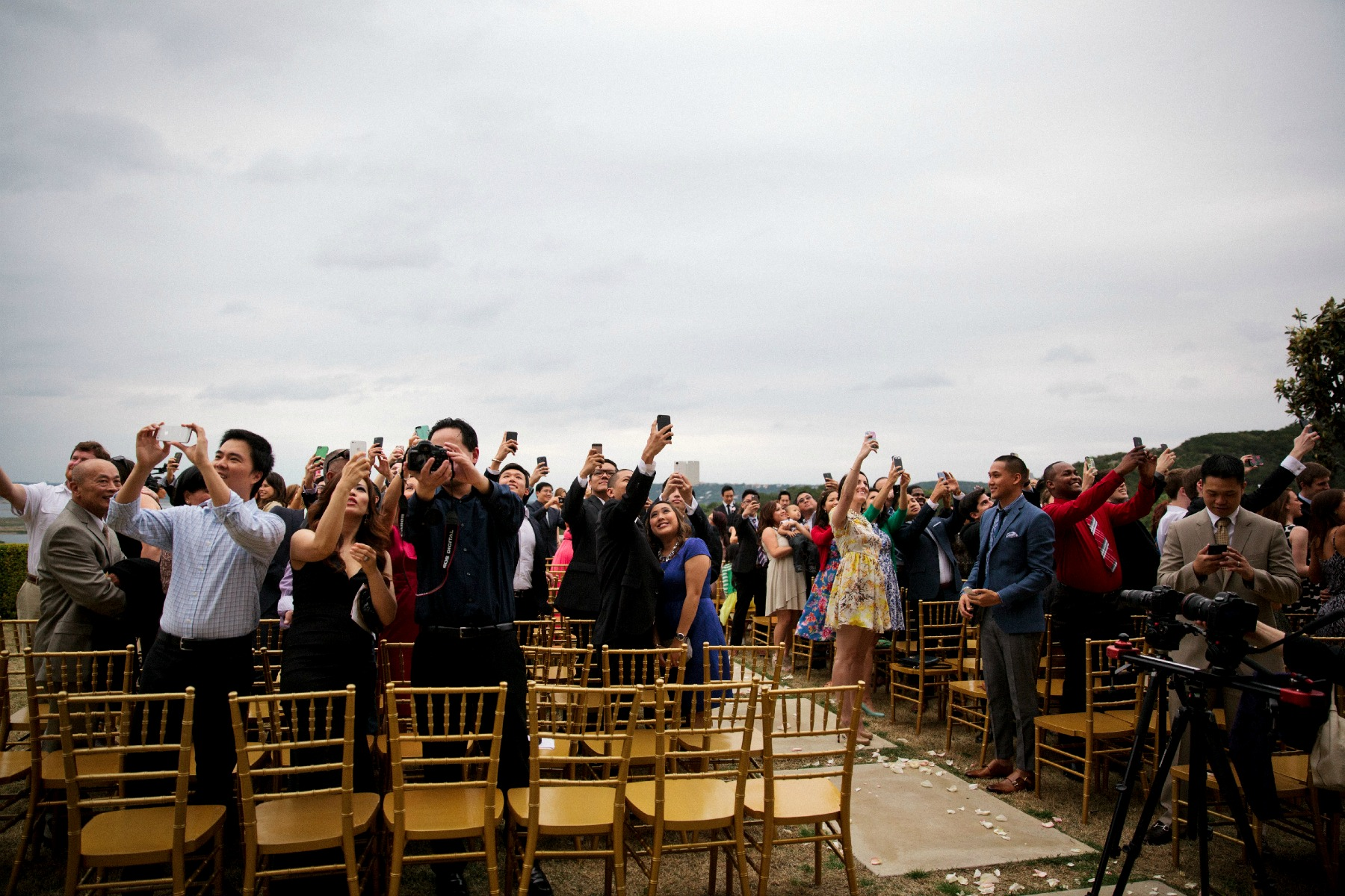 wedding guests all standing taking a selfie at the ceremony