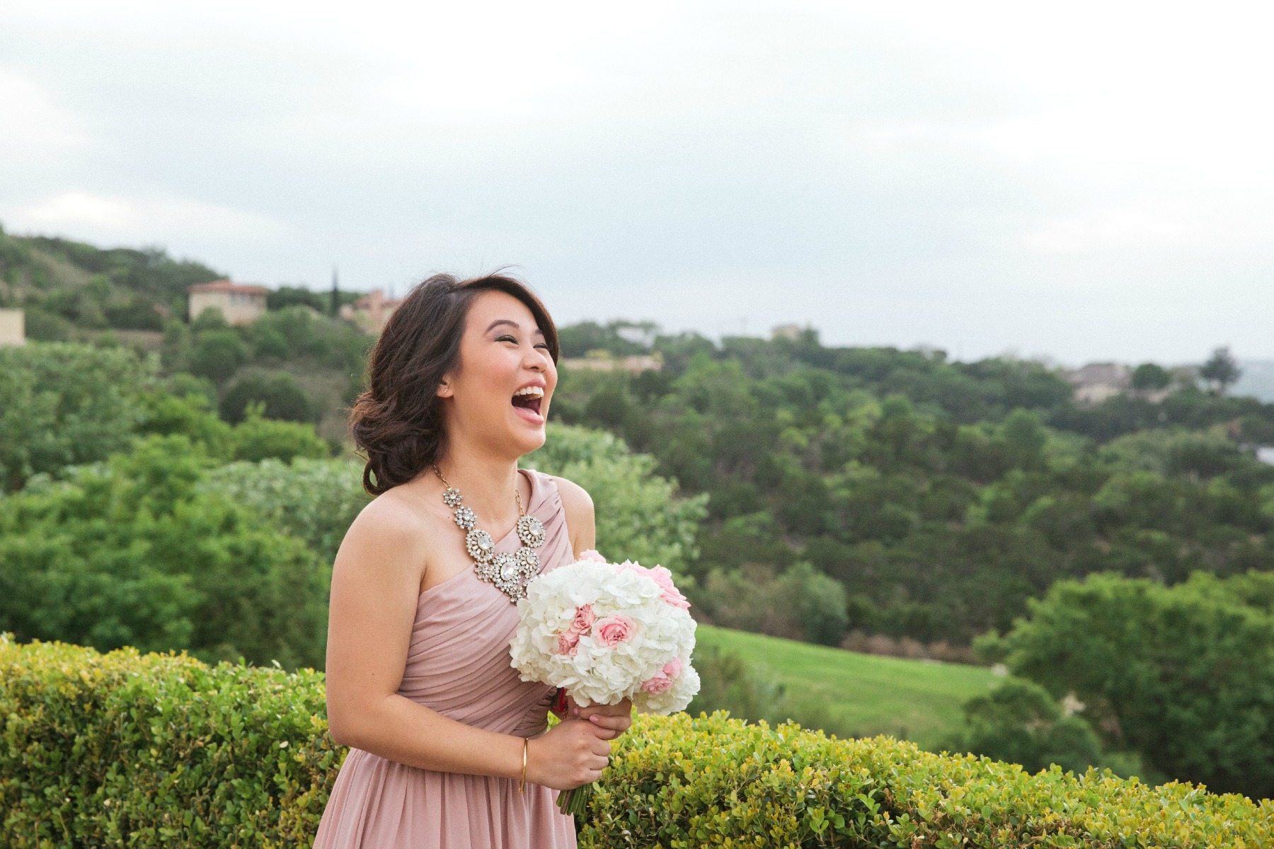 bridesmaid in pink dress laughing while holding her bouquet