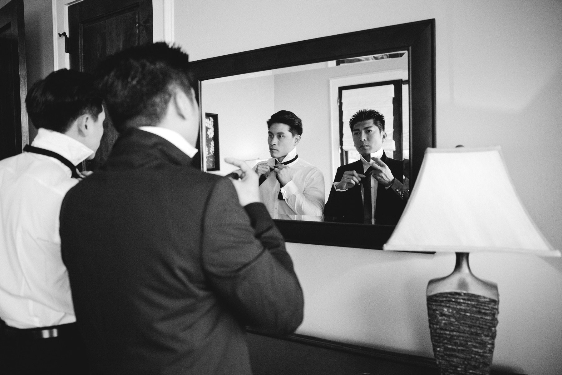 groom and best man tie their ties in front of mirror