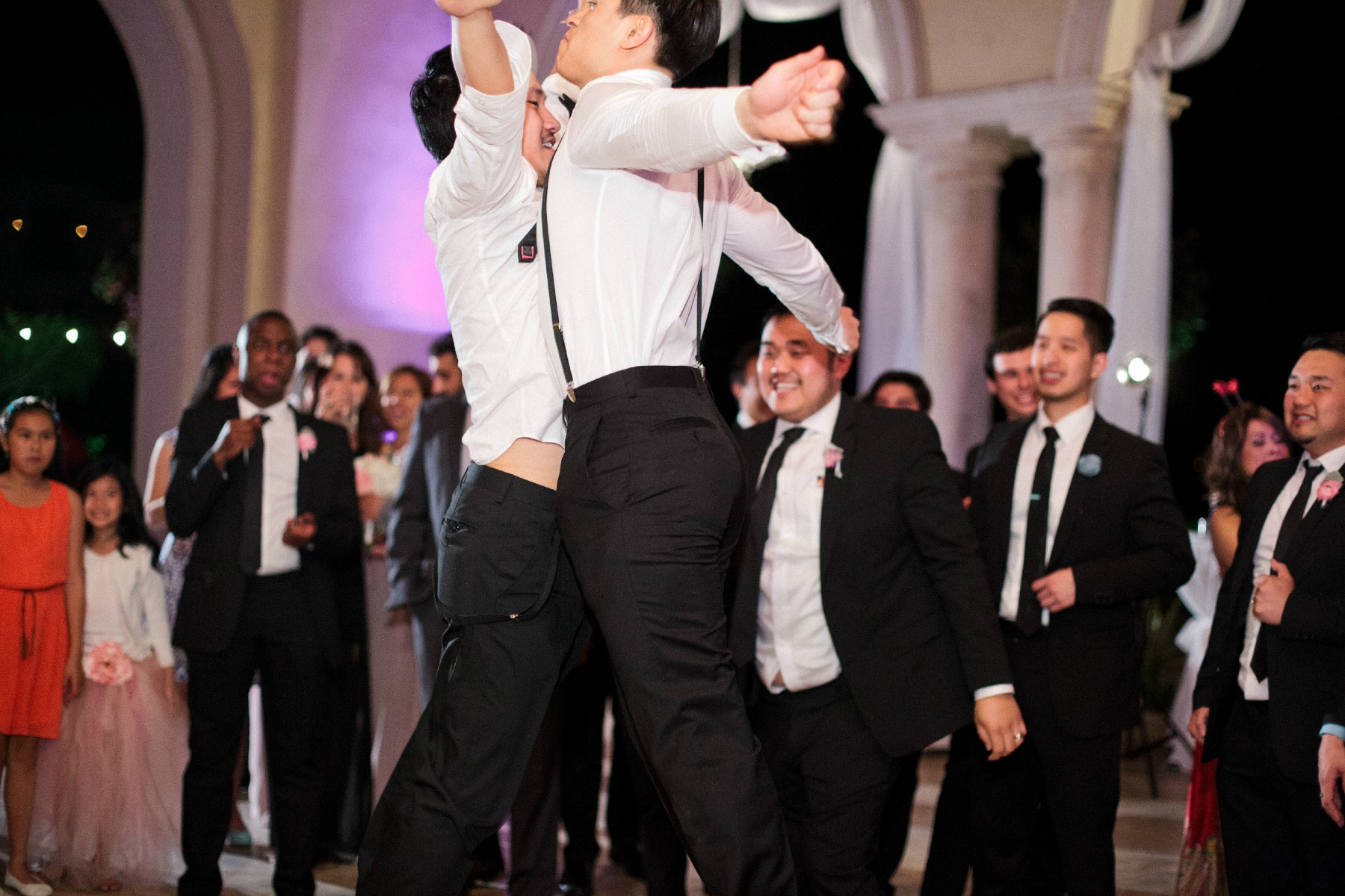 groom and groomsmen jump in the air and do a chest bump on the dance floor