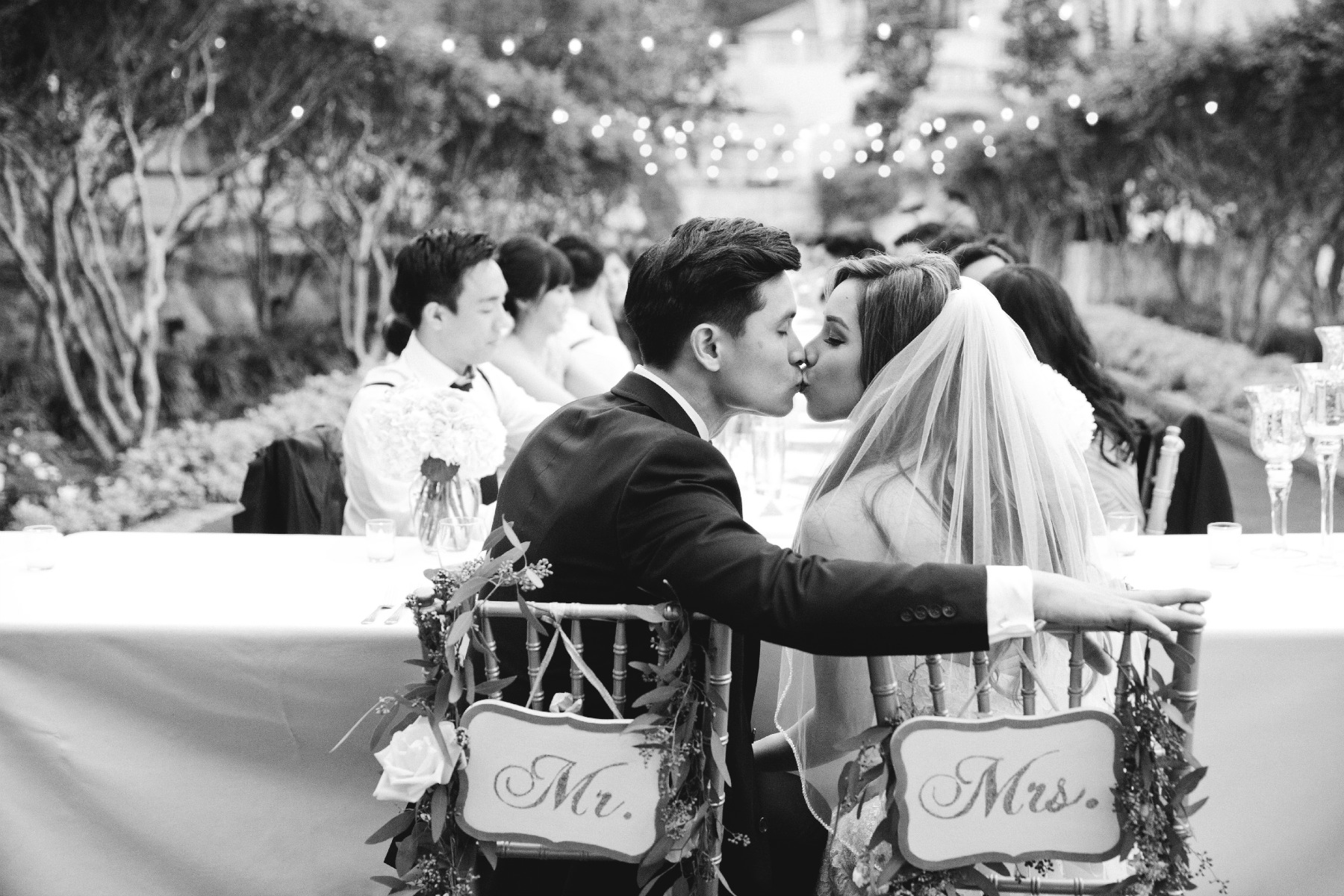 back shot of groom and bride kissing in Mr. and Mrs. chairs
