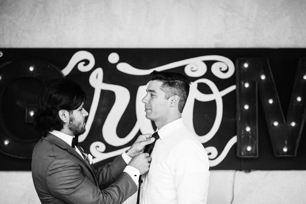 best man helping groom with his tie